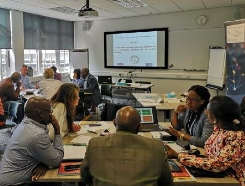 Image of workshop delegates discussing work, seated around tables.
