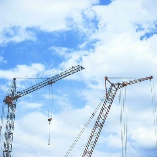 images shows tall construction cranes against a blue sky with clouds